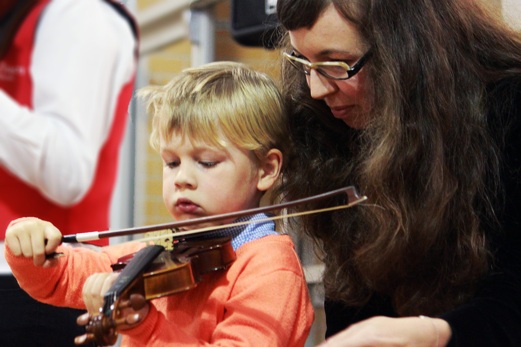 Mum helping her young violinist